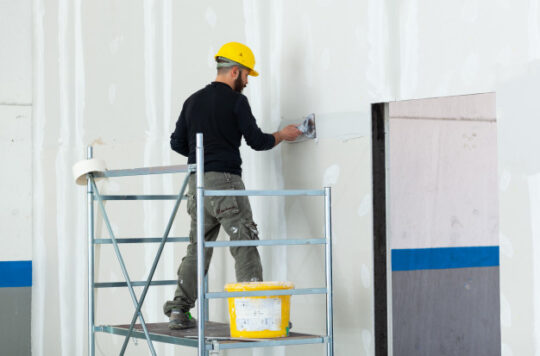 trabajador-enlucido-pared-tablero-drywall